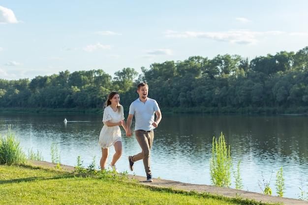 Natura estiva, relazione e concetto di persone innamorate - coppia felice che corre vicino al lago