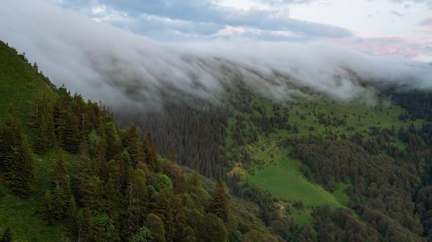 Paesaggio naturale estivo con nuvole basse sopra la collina all'alba.