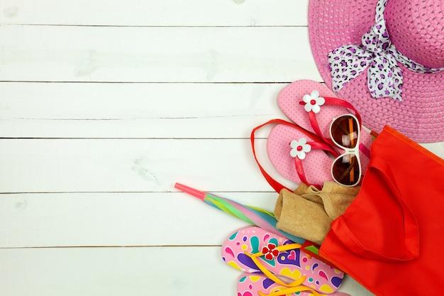 Oggetti estivi di cappello da donna, infradito, ombrello, asciugamano con accessorio estivo occhiali da sole su fondo di legno bianco.