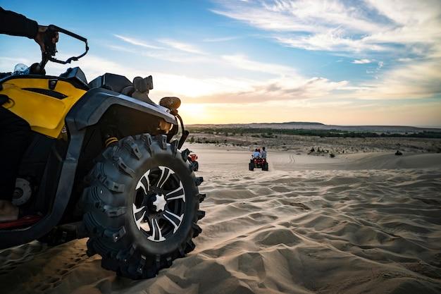 Avventura fuoristrada estiva su atv nella cava di sabbia. intrattenimento dei turisti nel deserto in mui ne in vietnam. primo piano della ruota dell'atv fuoristrada
