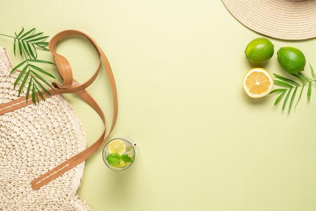 Estate pastello sfondo verde borsa di paglia e cappello per le vacanze calde limonata agrumi