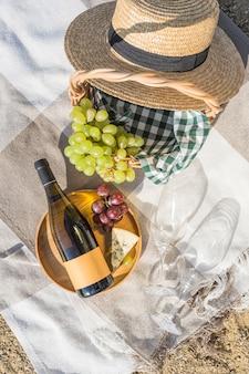 Picnic estivo sulla spiaggia con vino, formaggio e uva. vista dall'alto con uno spazio di copia. orientamento verticale.