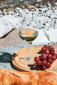 Picnic estivo sulla costa con bicchiere di vino bianco baguette ciliegie uva libro aperto cuscino da vicino