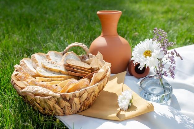 Picnic estivo sull'erba verde. brocca di argilla e pane