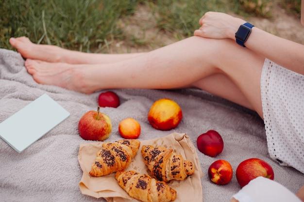Picnic estivo nella natura. la ragazza si siede su una stuoia e mangia le mele con i croissant