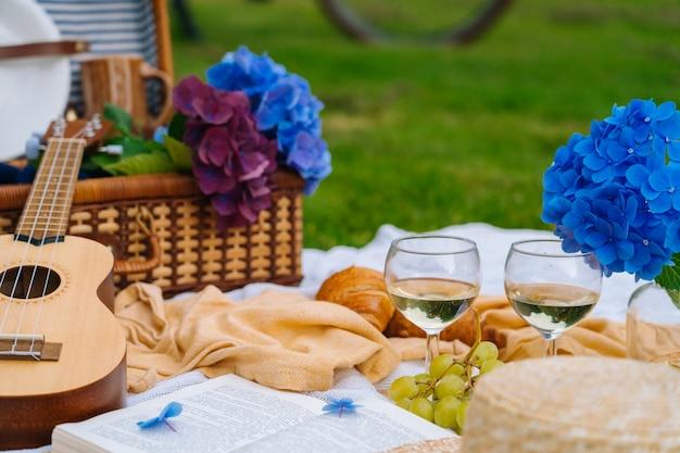 Picnic estivo in giornata di sole con pane, frutta, bouquet di fiori di ortensia, bicchieri di vino, cappello di paglia, libro e ukulele.