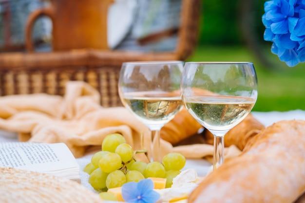 Picnic estivo in giornata di sole con pane, frutta, bouquet di fiori di ortensia, bicchieri di vino, cappello di paglia e libro.