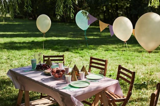 Tavolo da picnic estivo all'aperto decorato con palloncini per la festa di compleanno alla luce del sole copia spazio