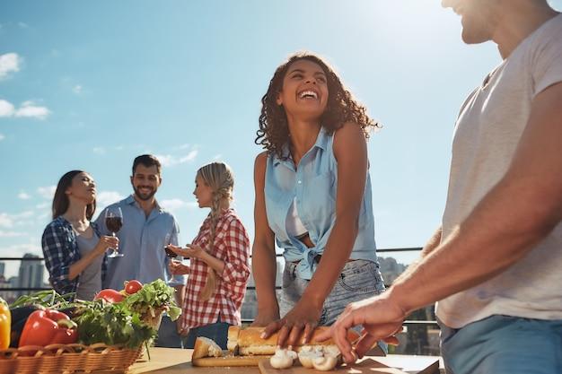 Picnic estivo due amici giovani e allegri in abiti casual che preparano cibo per la festa del barbecue