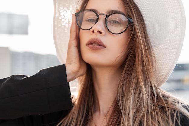 Ritratto estivo di una bella donna alla moda con gli occhiali con un cappello bianco e una giacca nera alla moda al tramonto. giovane ragazza in posa e guardando la telecamera
