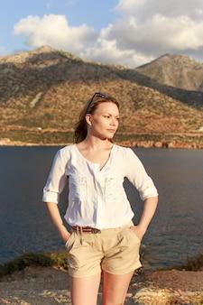 Ritratto di estate di bella ragazza in piedi vicino al paesaggio di mare e montagne.