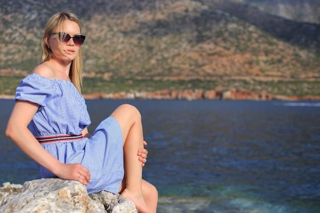 Ritratto di estate di bella ragazza in occhiali da sole che è seduto vicino al mare e alle montagne.