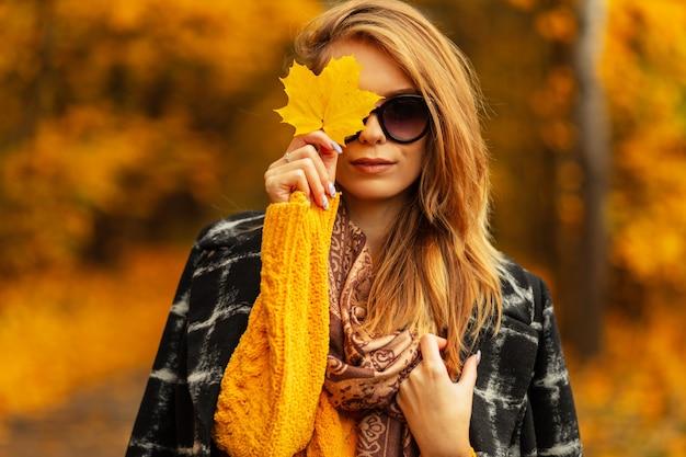 Ritratto di estate bella giovane donna in occhiali da sole in abito con cappello di paglia in città il giorno d'estate. attraente ragazza abbastanza elegante in abiti eleganti in posa sulla strada. la signora della bellezza si diverte.