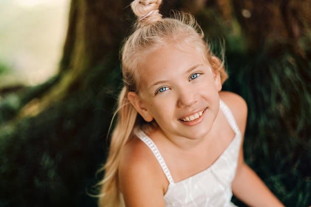 Ritratto di estate di una bambina felice sull'isola di mauritius. bel sorriso, abito bianco estivo.