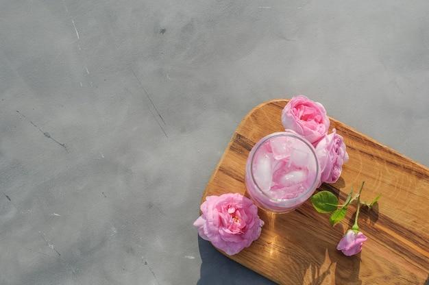 Bevanda rinfrescante estiva di rosa tea e cubetti di ghiaccio su tavola di legno su sfondo grigio gray