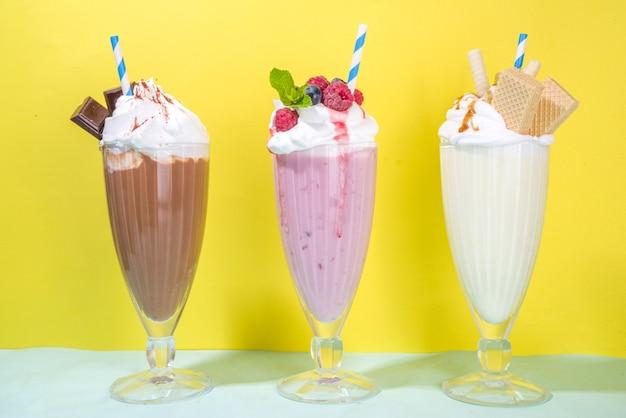 Bevande rinfrescanti estive, frappè, frullati pazzi con gelato, frutti di bosco, vaniglia, cioccolato. su uno sfondo giallo blu brillante