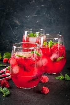 Cocktail analcolici rinfrescanti estivi. bevande alla frutta limonata al mojito di lamponi con menta e lime biologici freschi. su un tavolo di pietra nera. copia spazio