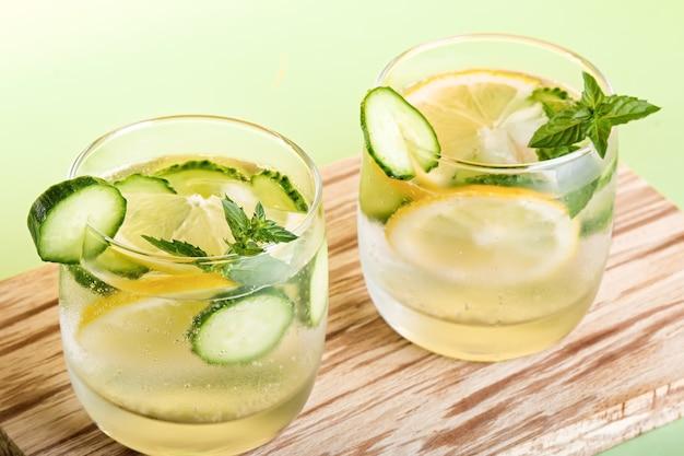 Cocktail analcolici rinfrescanti estivi con limone, cetriolo e menta, primo piano su sfondo giallo