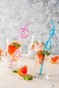 Bevanda disintossicante con acqua rinfrescante estiva con pompelmo rosa e menta fresca, acqua di frutta termale, limonata o jin tonic cocktail, sfondo chiaro