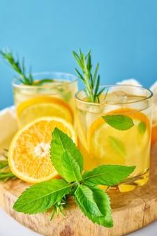 Bevanda rinfrescante estiva bicchiere d'acqua con menta arancione e rosmarino su sfondo blu