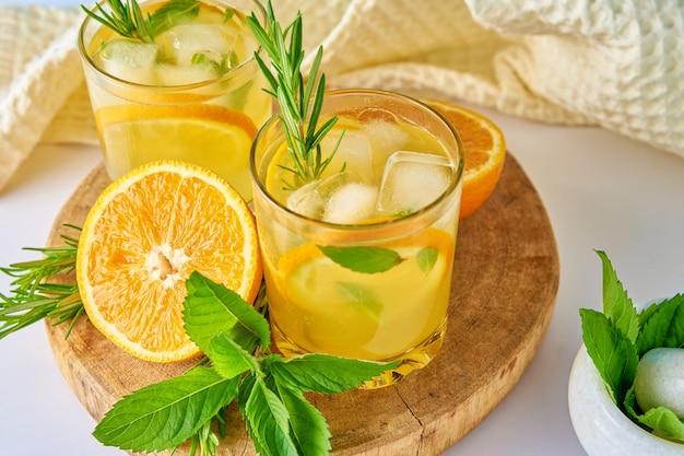 Bevanda rinfrescante estiva bicchiere d'acqua con menta arancia e rosmarino