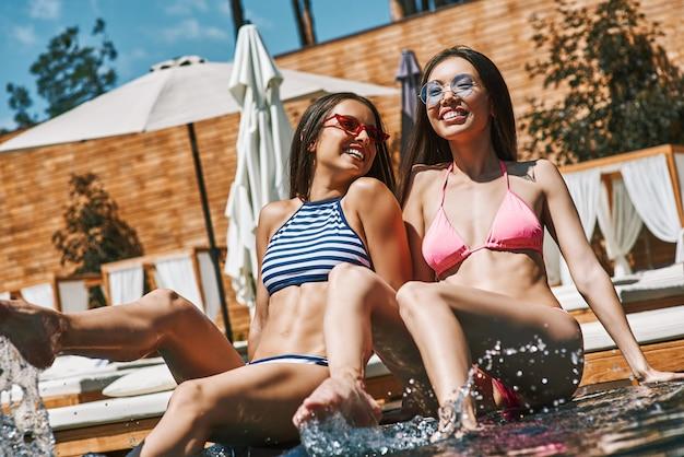 L'estate rilassa due giovani donne allegre e belle in bikini che sorridono e si godono il sole