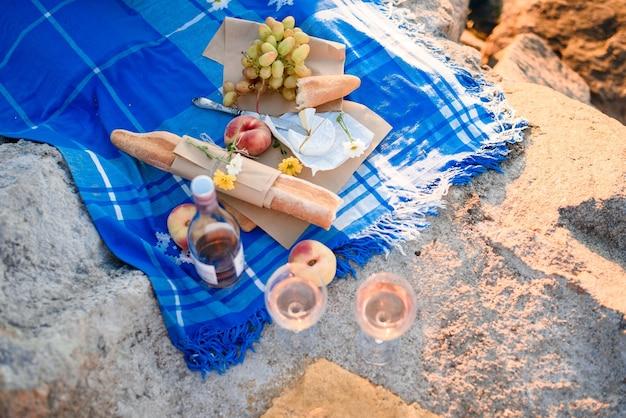 Picnic romantico estivo con frutta, formaggio, vino, pane, uva, pesche. luce dai primi raggi di sole.