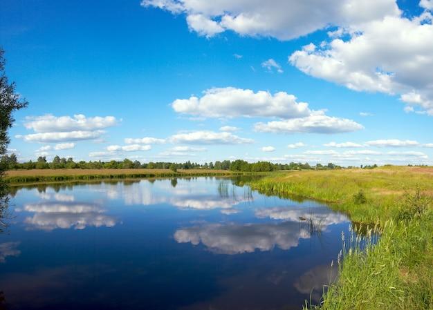 Estate rushy vista panoramica sul lago con riflessi di nuvole. un'immagine composita di tre colpi.