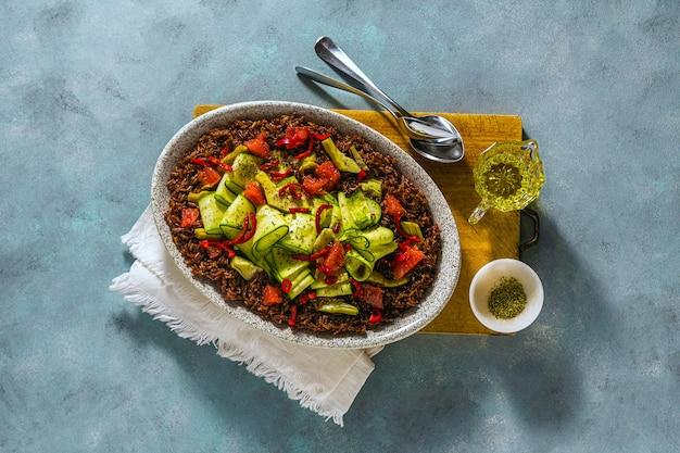 Insalata estiva di riso rosso, zucchine fresche e pompelmo con peperoncino e anacardi su sfondo blu