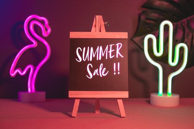 Saldi estivi sulla lavagna con luce al neon rosa e blu flamingo e cactus sul tavolo