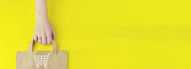Saldi estivi. l'e-commerce aggiunge al carrello il concetto di internet per lo shopping online. borsa della spesa in carta marrone riciclata in mano con ologramma icona del carrello su sfondo giallo. marketing digitale in linea.