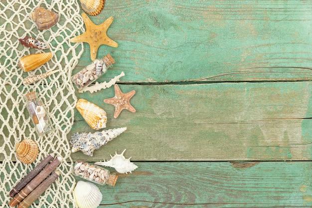 Vecchio fondo di legno del mare di estate con le conchiglie e le stelle marine della rete del mare