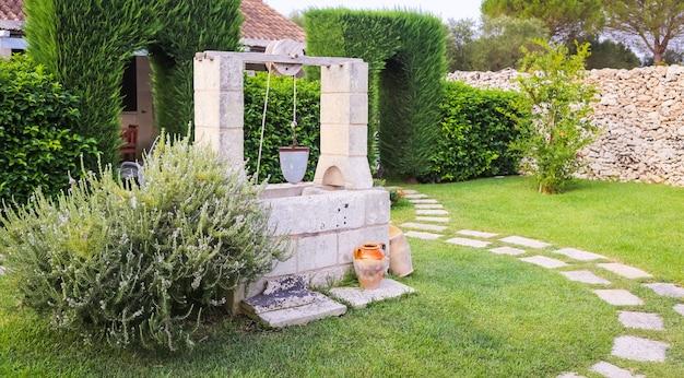 Stagione estiva in italia. progettazione di pozzo d'acqua in un elegante giardino.