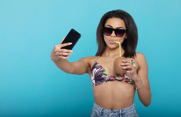Selfie estivo. ragazza nera in costume da bagno che si fotografa con il cocktail fresco sul cellulare.
