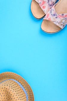 Scarpe estive e un cappello di paglia sulla superficie blu