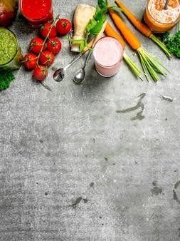 Frullati estivi con verdure fresche e frutta. su fondo rustico.