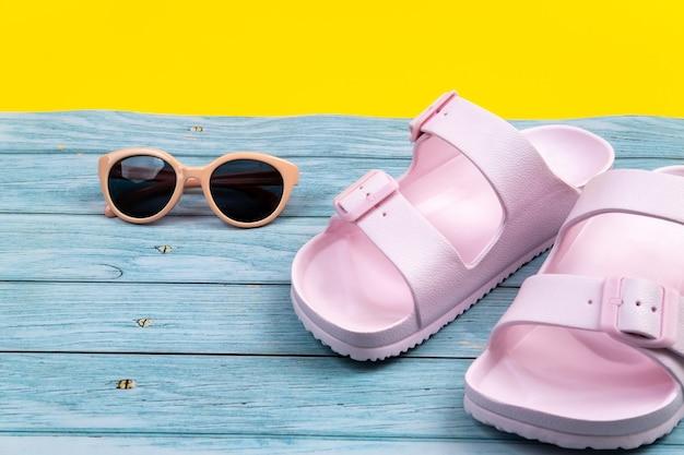 Le scarpe da ginnastica e gli occhiali estivi stanno su uno sfondo misto blu e giallo isolato
