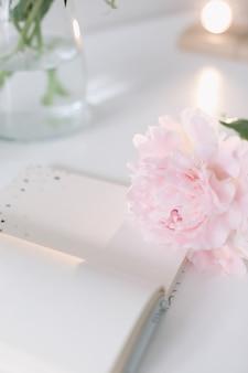 Natura morta estiva con fiori di peonia rosa e libro aperto