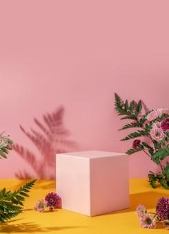 Stile estivo di vetrina per esposizione di prodotti cosmetici su sfondo giallo e rosa con fiori. piattaforma cubo rosa con fiori.