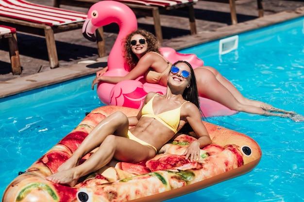 Stile estivo. donne su fenicottero rosa e pizza nell'acqua della piscina. modello di belle ragazze con un corpo sexy in bikini bianco alla moda che si rilassa sul materasso, godendosi l'estate.