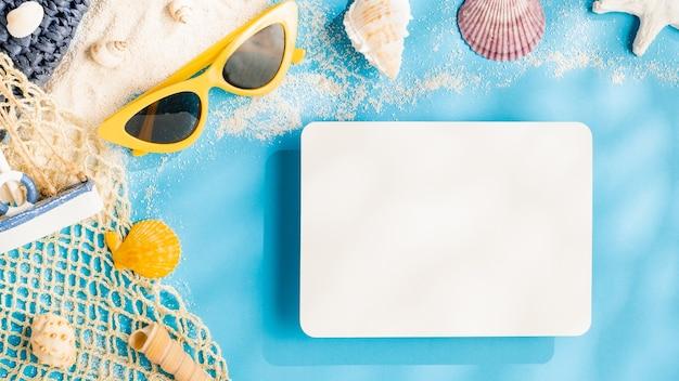 Concetto di luce solare estiva.carta di carta bianca sull'accessorio da spiaggia su sfondo blu del mare