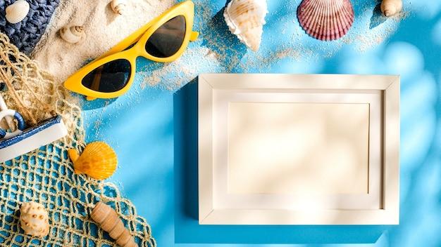 Concetto di luce solare estiva. carta cornice vuota sull'accessorio da spiaggia su sfondo blu del mare