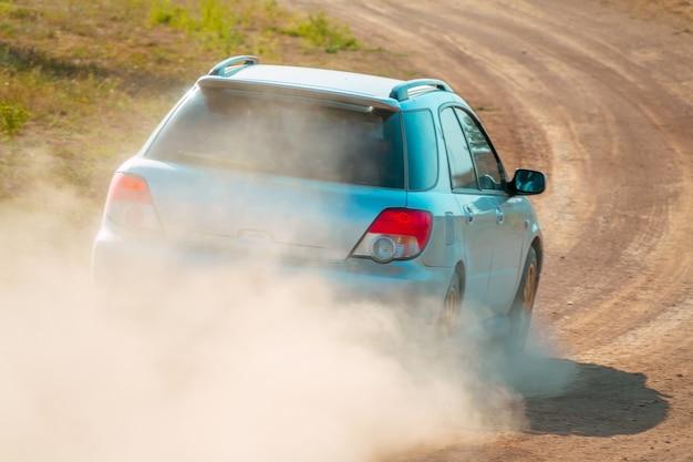 Giornata di sole estivo. l'auto da rally sta svoltando sulla strada sterrata. vista posteriore
