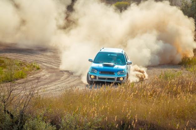 Giornata di sole estivo. l'auto da rally sta girando. tanta polvere
