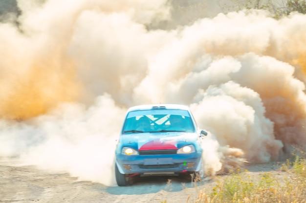 Giornata di sole estivo. auto da rally e svolta su una strada polverosa