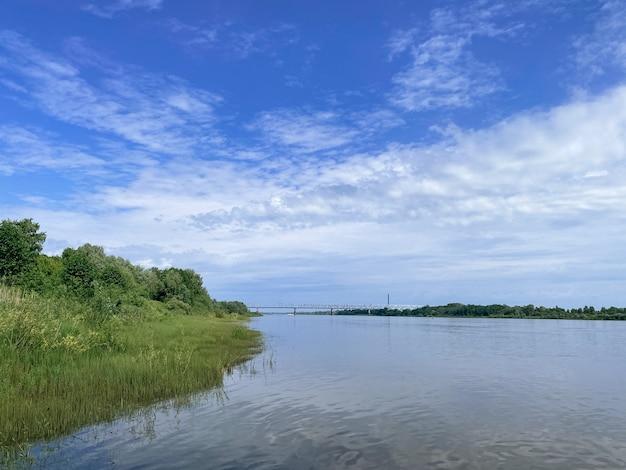 Paesaggio soleggiato estivo con nuvole in riva al fiume