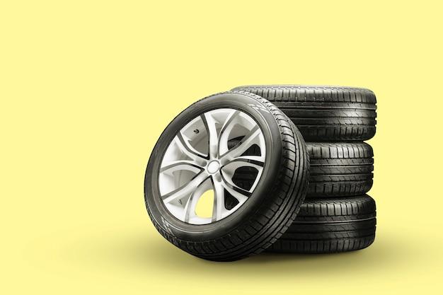 Pneumatici estivi e ruote impilate su sfondo giallo, ruote nuove.