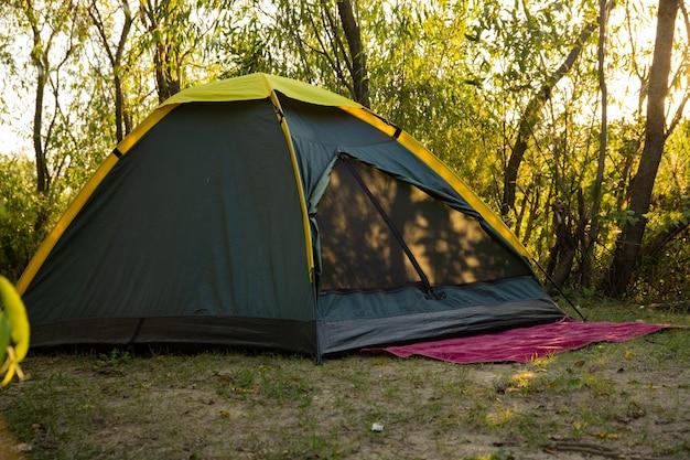 Tenda turistica estiva su uno sfondo di natura. il concetto di viaggio e attività all'aperto.