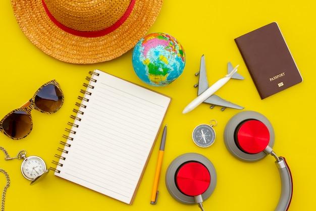 Accessori ed oggetti di viaggio di estate sullo spazio giallo della copia del fondo, per il viaggio di vacanza della spiaggia con il taccuino piano della macchina fotografica, per il manifesto di viaggio e la pubblicità dell'insegna