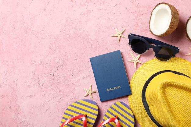 Accessori da viaggio estivi su rosa, spazio per il testo